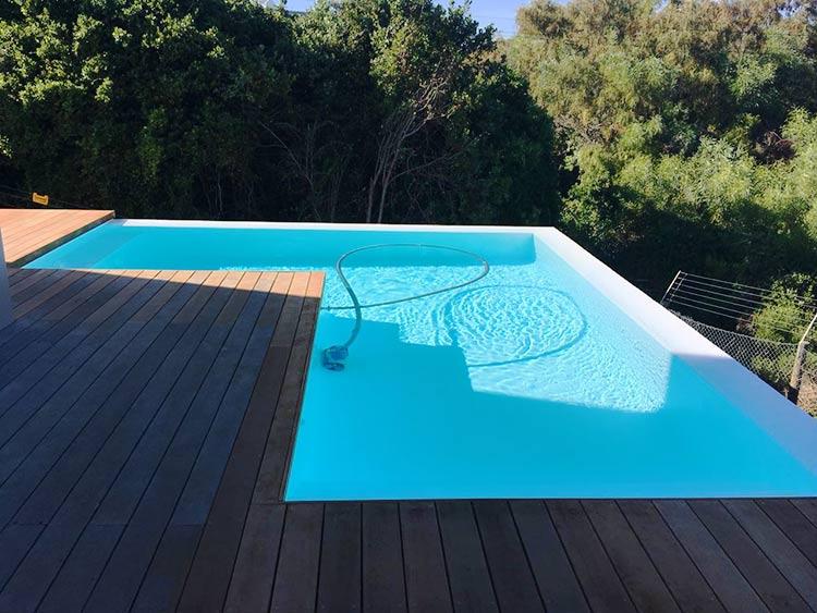 White fibreglass swimming pool with rim-flow.
